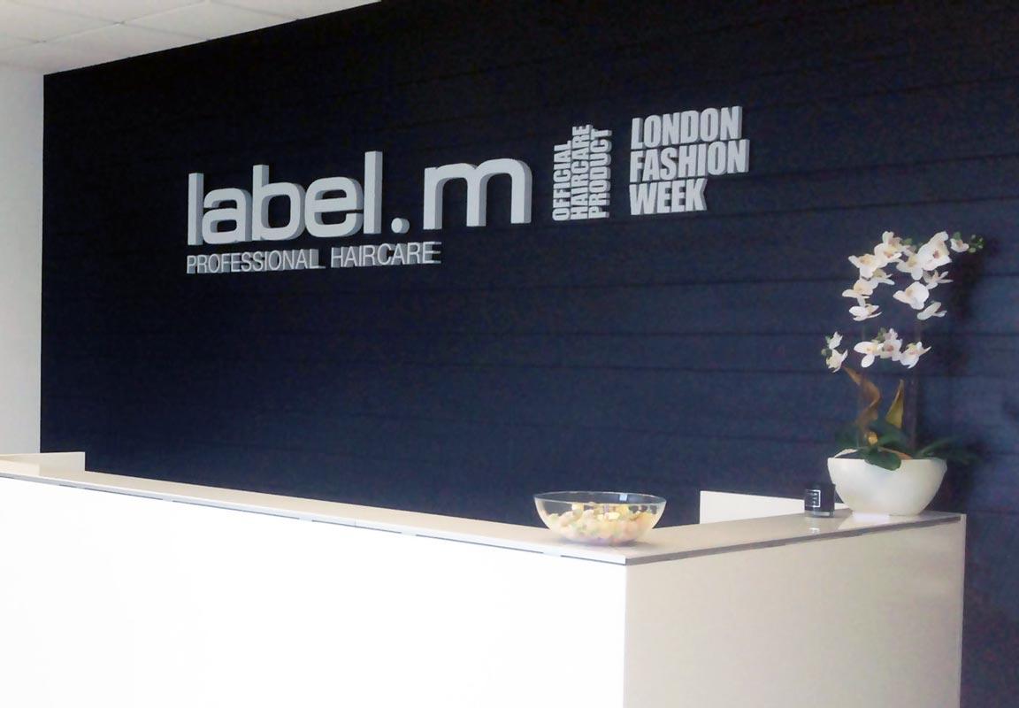 scritta in polistirolo 3d label.m sulla parete della reception